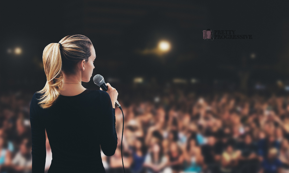 Back of Woman Giving Speech in Front of a Crowd
