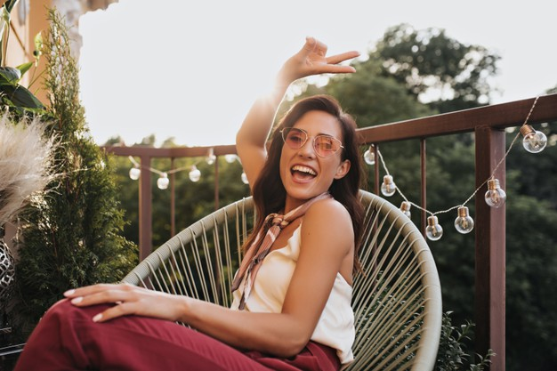 Brunette girl in pink glasses poses on balcony and shows peace sign. cheerful woman in silk scarf around her neck laughs and sits on terrace. Free Photo