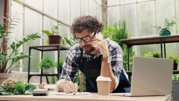 Man making business calls in a greenhouse.
