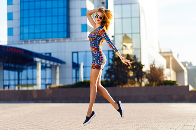 Outdoor portrait of amazing blonde woman wearing bright mini dress, city fashion street style. bright colors. Free Photo