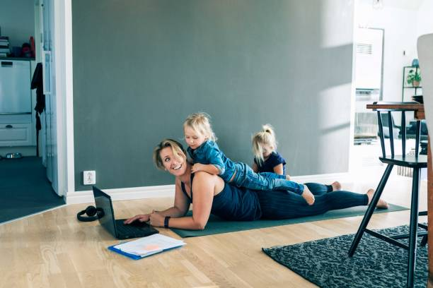 smiling mother with laptop looking at daughter lying on her back while girl sitting in living room at home - mum with kid stock pictures, royalty-free photos & images