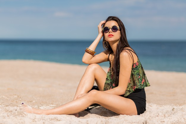 Woman in stylish tropical autfit posing on the beach. Free Photo